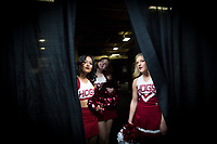 NWA Democrat-Gazette/CHARLIE KAIJO Arkansas Razorbacks cheerleaders peak through a curtain leading to the court during the Southeastern Conference Men's Basketball Tournament, Thursday, March 8, 2018 at Scottrade Center in St. Louis, Mo.