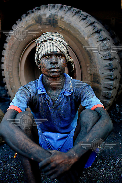 A contract labourer sits infront of the wheel of one of the trucks that he spends 10 - 12 hours each day filling, at an open cast mine, with rock coal. For this he'll earn less than GBP 2.20. /Felix Features