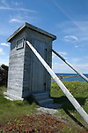 Outhouse on seashore at Western Brook, Newfoundland, supported against prevailing coastal winds