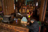 An old man sits quietly in front of the statues of the Medicine God as he believes the deity is checking his health and will later disclose his health situation by drawing a number at the altar of the Temple of Medicine God in Tainan, Taiwan, 2015.