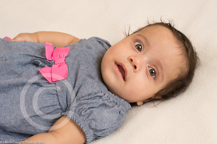 4 month old baby girl closeup on back startled expression