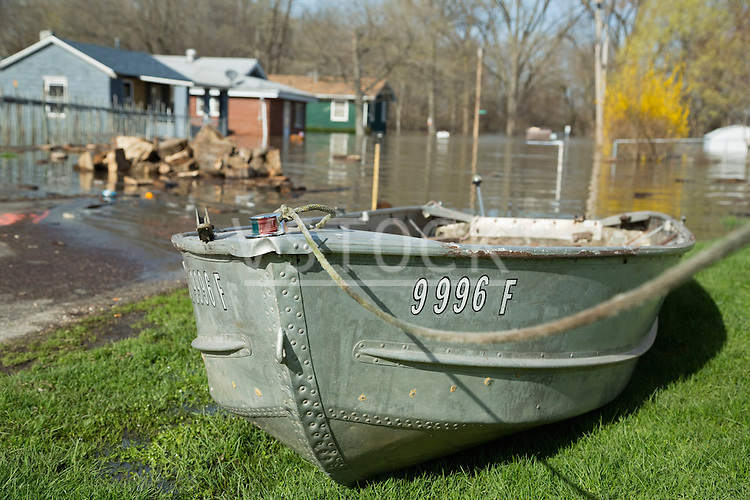 Rowboat on lawn near flooded street
