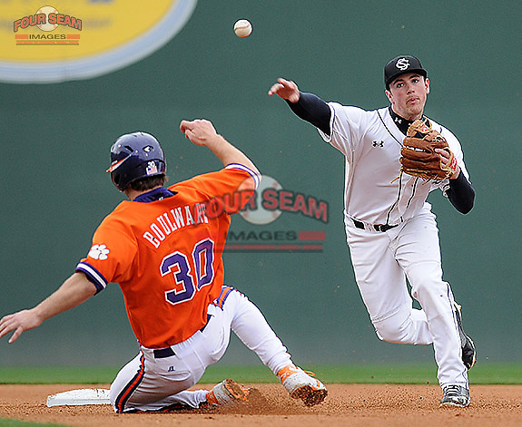 Shortstop Joey Pankake (9) of the South Carolina Gamecocks turns a double play, as Garrett Boulware slides in a game against the Clemson Tigers on Saturday, March 2, 2013, at Fluor Field at the West End in Greenville, South Carolina. Clemson won the Reedy River Rivalry game 6-3. (Tom Priddy/Four Seam Images)