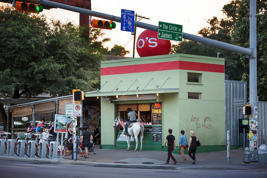 A man on horseback stops at a South Congress coffee stand for a cappuccino - Stock Image.