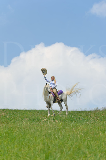 Woman on white horse waving her cowboy hat in cheerful greeting, full western wear against a big open sky.