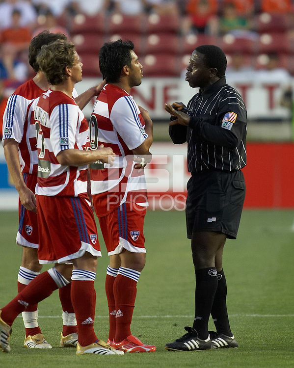 FC Dallas' Carlos Ruiz (20) discusses a call with referee Abiodun Okulaja while teammates Simo Valakari (17) and Mark Wilson (15) attempt to calm the waters at Robertson Stadium in Houston, TX on Saturday May 6, 2006. The Houston Dynamo defeated FC Dallas 4-3.