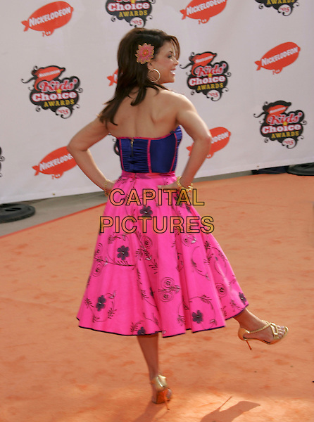 PAULA ABDUL.Attends Nickelodeon's 18th Annual Kids' Choice Awards Show held at UCLA's Pauley Pavilion in Westwood, California, April 2nd 2005..full length strpless corset top dress pink fucshia skirt hans on hips flower in hair printed patterned floral peacock feather gold bracelets bangle blue gold strappy sandals shoes kicking leg foot funny.Ref: DVS.www.capitalpictures.com.sales@capitalpictures.com.©Debbie VanStory/Capital Pictures