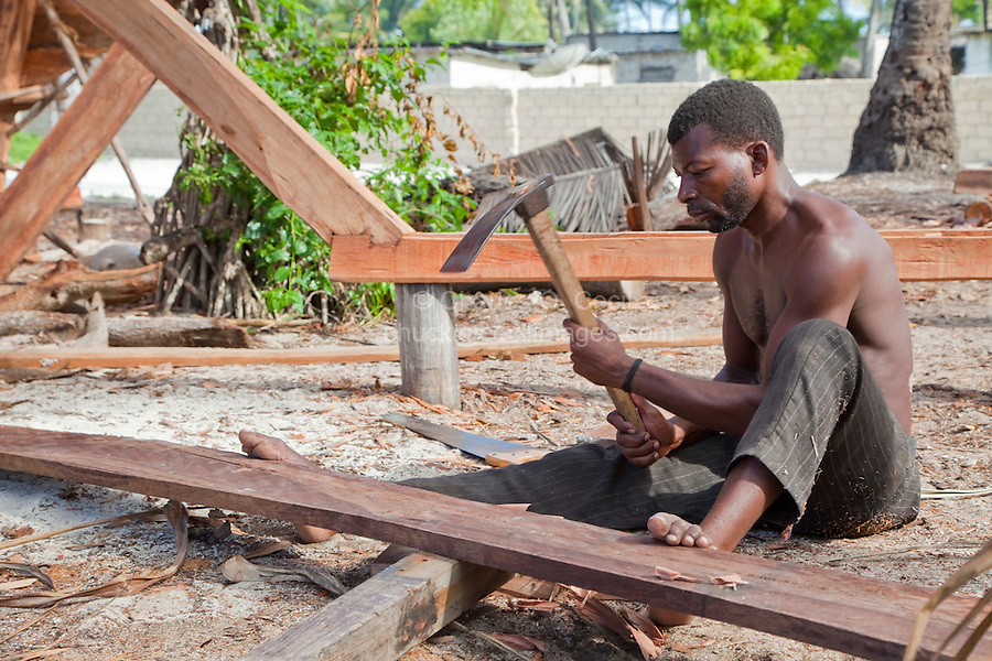 Nungwi, Zanzibar, Tanzania.  Dhow Construction, Boat Building.  Carpenter Using an Adze to Smooth a Plank.