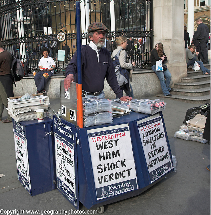 Newspaper seller at stand, Liverpool Street station, London, with news of West Ham FC being fined and Spring heatwave late April 2007