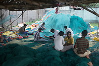 Fisherman repairing fishing net at a village in Cuddalore which was devastated by 2004 Tsunami. Tamil Nadu, India.