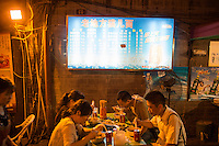 People eat at Lao Di Feng Mao Er Mien near Ciqikou ancient town in the Shapingba district of Chongqing, China. These snacks are usually eaten while drinking beer. The restaurant is primarily outdoors and is open 24 hours a day. The restaurant has been for about 10 years. At night, the restaurant serves mostly neighborhood locals. <br /> <br /> Ciqikou's ancient town is a major tourist destination in Chongqing, but at night, the tourists disappear and locals come out to eat from street food vendors in the area.