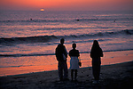 Family watching sunset over ocean Carlsbad,+Northern San Diego Coastline San Diego County, CALIFORNIA