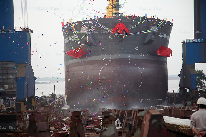 Workers watch as the 57,000 dead weigh ton bulk carrier Sabina Venture slids into the Yangzte River at the China CSSC Holdings Ltd. Chengxi Shipyard in Jiangyin, China, on Sunday, Sept. 12, 2010. China CSSC Holdings Ltd., the nation's biggest shipyard, sees orders surge as China's voracious appetite for commodities demands more fleets of large vessels.