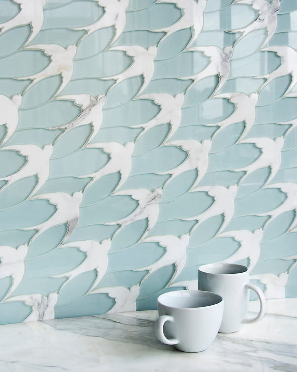 Flock®, a stone and Serenity glass waterjet mosaic, shown in Infinity Serenity glass and polished Calacatta, is part of the Altimetry® collection for New Ravenna.