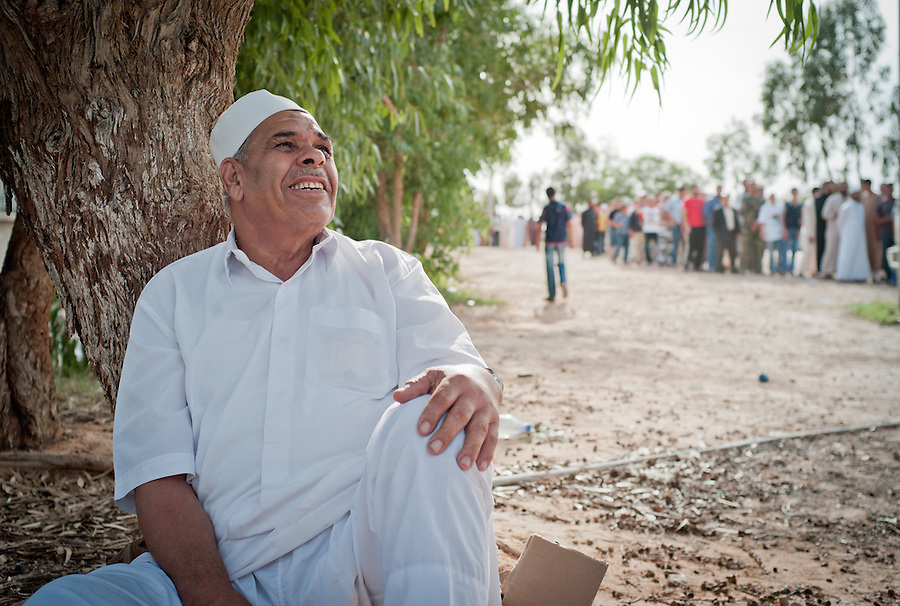 Libyan man sits under a tree while people queue to view the body of Muammar Gaddafi at the African Tunisian Souq in Misrata, Libya, Saturday October 22, 2011. The confirmed death of Muammar Gaddafi brings closure to an 8 month uprising turned revolutionary war.