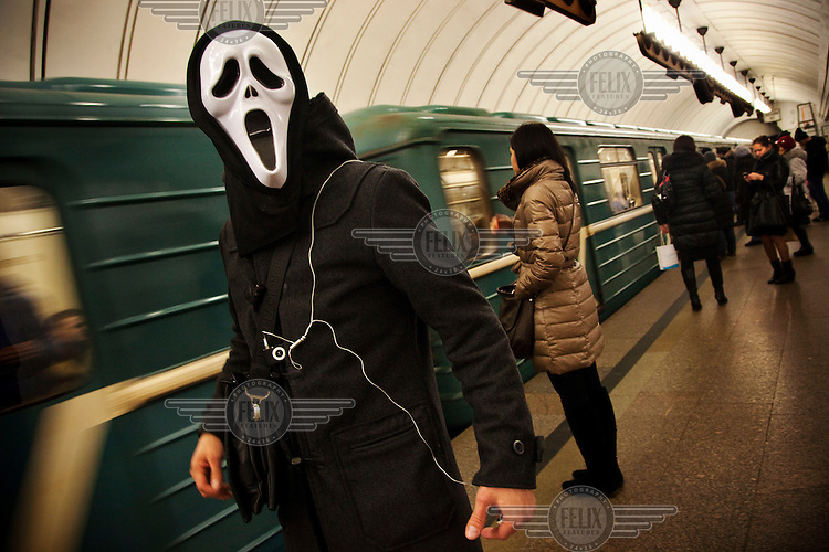 A man wearing a mask from the film 'Scream' stands on the platform of a metro station in Moscow.