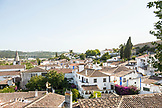 PORTUGAL, Obidos, White washed buildings and red rooftops of the old city. Green hills in the background