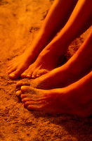 Closeup of a man & woman's feet in the sand together