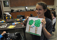 NWA Democrat-Gazette/FLIP PUTTHOFF <br /> PROUD ARTIST<br /> Addey Hester shows her finished art work Wednesday March 23, 2016 during Spring Break Day Camp  at Hobbs State Park-Conservation Area. Students take part in a variety of nature activities with guidance from Rebekah Penny, park interpreter, and Caitlin Mitchell, college intern. The park also hosted dozens of students from Camp War Eagle on Wednesday who did trail work on the Dutton Hollow Loop of the park's multiuse trail for hikers, horse-back riders and mountain bikers.