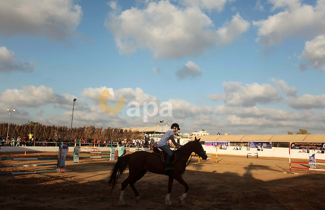 A Palestinian horse rider takes part in a jumping competition in Gaza city on June 12, 2015. The competition organized by Gaza equestrian club participant by 35 rider from the besieged coastal enclave. Photo by Ashraf Amra