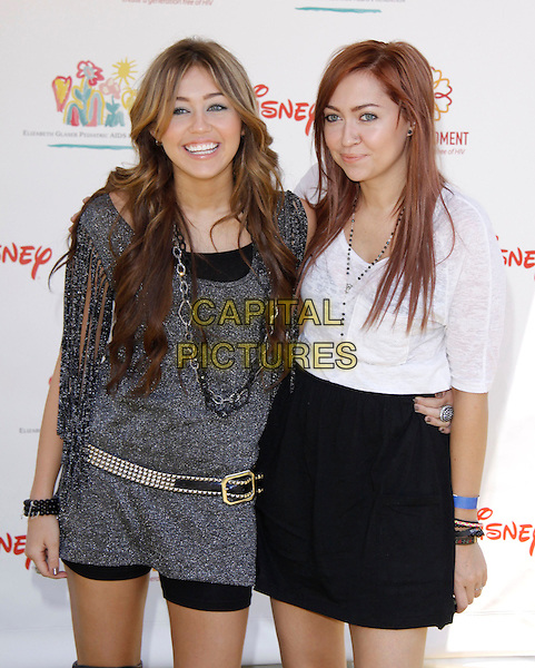 "MILEY CYRUS & BRANDI CYRUS.The 20th annual ""A Time for Heroes"" Celebrity Carnival benefiting Elizabeth Glaser Pediatric AIDS Foundation held at Wadsworth Theater on the Veteran Administration Lawn in West Los Angeles, California, USA. .June 7th, 2009.half length black grey sparkly gray silver dress tassels belt chains necklace white top skirt sisters siblings family .CAP/DVS                                                  .©Debbie VanStory/Capital Pictures."