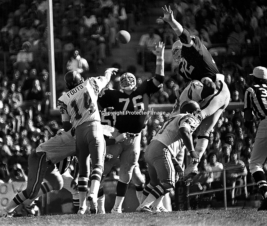 Oakland Raiders defense puts a rush on San Diego Charger QB Dan Fouts...#76  Mike McCoy amd #72 John Matuszak..(1978 photo/Ron Riesterer)