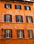 Fading, patchy paint adds color to the shuttered windows of an old apartment building in central Rome, Italy.