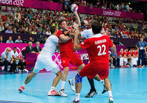 29 JUL 2012 - LONDON, GBR - Steve Larsson (GBR) of Great Britain (second from left, in red) finds his path to goal blocked by Jerome Fernandez (FRA) (left) and Didier Dinart (FRA) of France (second from right) during the men's London 2012 Olympic Games Preliminary round handball match at The Copper Box in the Olympic Park, in Stratford, London, Great Britain (PHOTO (C) 2012 NIGEL FARROW)