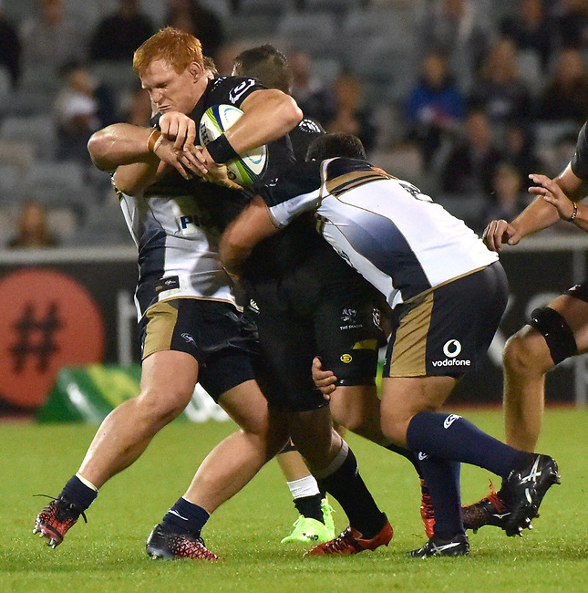 Sharks player Philip van der Walt is tackled by Brumbies players  during the Super Rugby match between the ACT Brumbies and the South African Sharks in Canberra on March 4, 2017. AFP PHOTO / MARK GRAHAM --- IMAGE RESTRICTED TO EDITORIAL USE - STRICTLY NO COMMERCIAL USE --