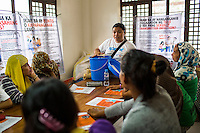 Pregnant women and lactating mothers listen to a SPRINT-IPPF are introduced to the dignity kits during a reproductive health (RH) information session at a RH Medical Mission in the Taluksangay Barangay Hall, Zamboanga, Mindanao, The Philippines on November 5, 2013. These Internally Displaced People (IDP) had taken refuge in this Barangay (neighbourhood) after surviving the 3 week long attack by MNLF rebels. Photo by Suzanne Lee for SPRINT-IPPF