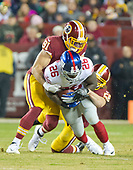 New York Giants running back Orleans Darkwa (26) is tackled by Washington Redskins outside linebacker Ryan Kerrigan (91) and linebacker Junior Galette (58) in first quarter action at FedEx Field in Landover, Maryland on Thursday, November 23, 2017.<br /> Credit: Ron Sachs / CNP<br /> (RESTRICTION: NO New York or New Jersey Newspapers or newspapers within a 75 mile radius of New York City)
