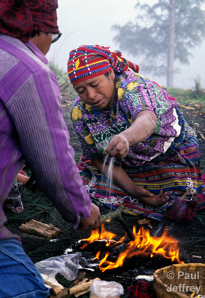 Pouring sugar on a fire, a K'iche' Maya woman priestess leads an indigenous spiritual ceremony near San Andres Xecul, Guatemala.