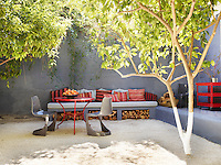 A sunny courtyard terrace with 1966 Steen Ostergaard chairs and a table designed by Sameul Dowe-Sandes. A row of cushions in re purposed kilim sit atop a bench seat with logs stored below.