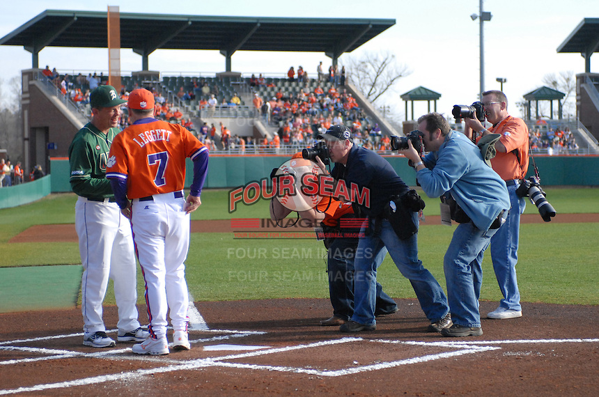 Photographers jockey for position to photograph head coach Jack Leggett (7) of the Clemson Tigers and head coach Brian Shoop of the University of Alabama-Birmingham on Feb. 17, 2012, at Doug Kingsmore Stadium in Clemson, South Carolina. (Tom Priddy/Four Seam Images)