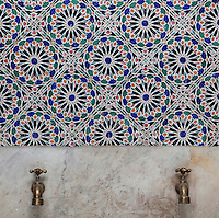 A zellige tilework wall with repeating floral motif and below, a fountain with 2 taps, in the central courtyard area of a typical Tetouan riad, a traditional muslim house built around a courtyard, built in Moorish style with strong Andalusian influences, next to the Great Mosque or Jamaa el Kebir in the Medina or old town of Tetouan, on the slopes of Jbel Dersa in the Rif mountains of Northern Morocco. Tetouan was of particular importance in the Islamic period from the 8th century, when it served as the main point of contact between Morocco and Andalusia. After the Reconquest, the town was rebuilt by Andalusian refugees who had been expelled by the Spanish. The medina of Tetouan dates to the 16th century and was declared a UNESCO World Heritage Site in 1997. Picture by Manuel Cohen