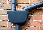 Plastic drainpipes on red brick wall