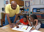 Berkelely CA 5th grade African American male teacher evaluating students' geography work with them