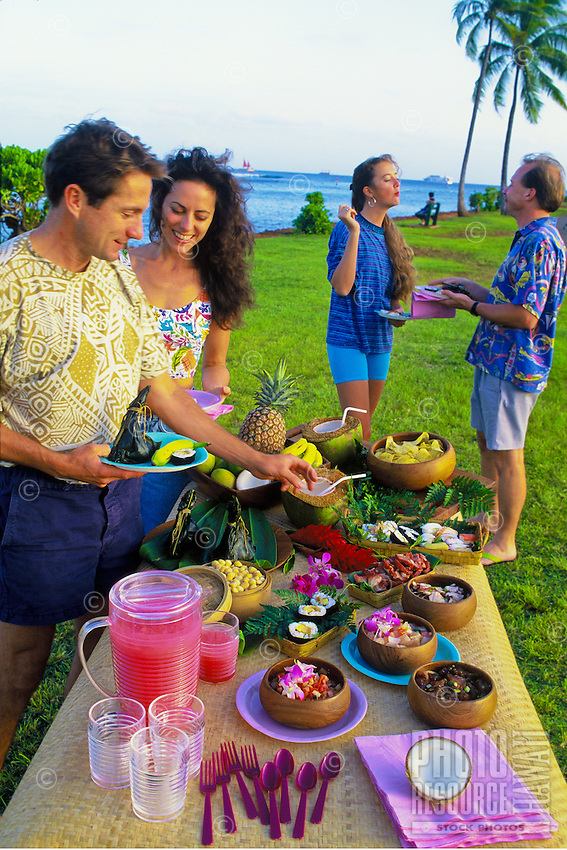 Outdoor buffet luau picnic with two couples near beach, Magic Island, Oahu, Hawaii