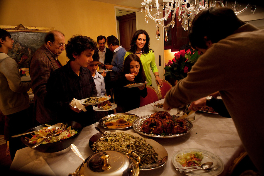 Los Angeles, California, March 20, 2011 - Sharona Nazarian (upper right in cardigan) looks over the meal she prepared to celebrate Nowruz, the Persian New Year and the Jewish holiday Purim. The Persian calendar solar while the Jewish calendar is lunar, but in certain years the two holidays coincide.  ..Nowruz, the Persian New Year, marks the first day of spring and the beginning of the Persian calendar. It is marked by Haft Sin, or the seven S's, which include sabzeh (wheat, barley or lentil sprouts growing in a dish - symbolizing rebirth); samanu (a sweet pudding made from wheat germ -symbolizing affluence); senjed (the dried fruit of the oleaster tree - symbolizing love); s?r (garlic - symbolizing medicine); s?b (apples - symbolizing beauty and health); somaq (sumac berries - symbolizing the sunrise); serkeh (vinegar - symbolizing age and patience). Each of these items are laid on a table in the home. Other items include decorated eggs, symbolizing fertility, a mirror symbolizing cleanliness and honesty and a bowl with goldfish, symbolizing life within life. ..Purim is a Jewish holiday that commemorates the deliverance of the Jewish people living in the Persian Empire from genocide at the hands of the political advisor, Haman, to the Persian King Ahasuerus, as documented in the Talmud's Book of Esther. It is celebrated by the reading of the Scroll of Esther or the Megillah, sending food gifts to friends, giving charity to the poor and celebrating with a festive meal. During the reading of the Megillah, when Haman's name is mentioned (which happens 54 times) the congregation engages in loud roars and the use of rattles in an effort to blot out his name. Today children and some adults dress in costume and masquerade to celebrate Purim. The custom is believed to have originated during the 15th century by Italian Jews influenced by the Roman carnival. One idea for the costumes is that God disguised his presence behind many of the natural events that happened during Pu