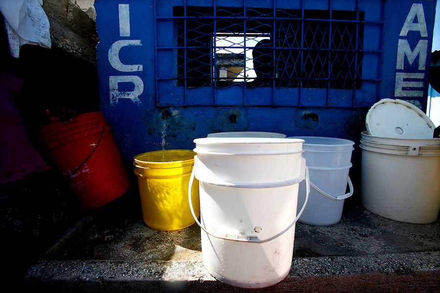 Nov 10, 2010 - Port-au-Prince, Haiti.Locked in a small enclosure, a man sells fresh water to residents of the Cite Soleil area of Port-au-Prince, Haiti on Wednesday, November 10, 2010 as fears of a Cholera outbreak spread through the area just two days after cases of the infection were confirmed in the area, the poorest slum in Haiti's capital. Officials from the Pan American Health Organization warn that Haiti's cholera epidemic, spread primarily through consuming infected water and food, is likely to grow much larger in the wake of Hurricane Tomas.  (Credit Image: Brian Blanco/ZUMA Press)