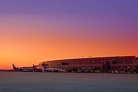 A beautiful vibrant sunset greets Austin–Bergstrom International Airport as passenger jets are lined up at their gates. ABIA is an international airport serving Austin, Texas - Stock Image.