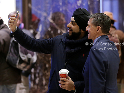 Retired United States Army lieutenant general Michael T. Flynn takes a photo with a man at Trump Tower on December 5, 2016 in New York City. United States President-elect Donald Trump is still holding meetings upstairs at Trump Tower as he continues to fill in key positions in his new administration.   <br /> Credit:John Angelillo / Pool via CNP