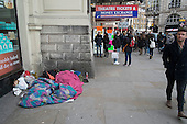 Two homeless rough sleepers and pedestrians, Piccadilly Circus, London.