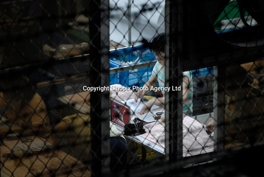 A worker seen through a window makes puma shoes at the Yuen Yue shoe factory complex where 100,000 workers make shoes in Gao Bu Town, near Dongguan in Guangdong, China. The complex makes shoes for shoe makers including Puma, Adidas and Nike amongst others..06 Sep 2006