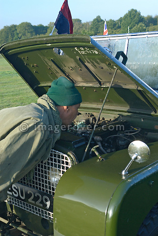 Adrian Cussack curiously inspectiong a 1949 Rolls Royce engine powered Series 1 81in Land Rover. Exhibited at Dunsfold Collection of Land Rovers 2006 open day, Dunsfold, Surrey, England, UK.  --- No releases available. Automotive trademarks are the property of the trademark holder, authorization may be needed for some uses. --- Information: Rolls Royce engine powered Series 1 81 inch Land Rover, belonging to the REME Corps Museum: chassis number R06104455, registration number ESU229, engine type ROLLS ROYCE 3.0 L, gearbox type 4-speed. Vehicle History: This is one of 33 Series 1 Land Rover 80 inch wheelbase vehicles that were converted to Rolls Royce engines in 1949. The cats were converted by Hudson Motors in London. To allow the engine to fit the springs were upgraded, and transfer box, front panel, floor, exhaust, gauges and many more bits modified. The rear axle was moved back by 1 inch, making them known as the 81in Land Rovers. After trials the project was dropped. This vehicle was one of two converted after trials to a parade vehicle. It has been at the Beverly Museum until 2006 then passed over to the R.E.M.E. Corps Museum.