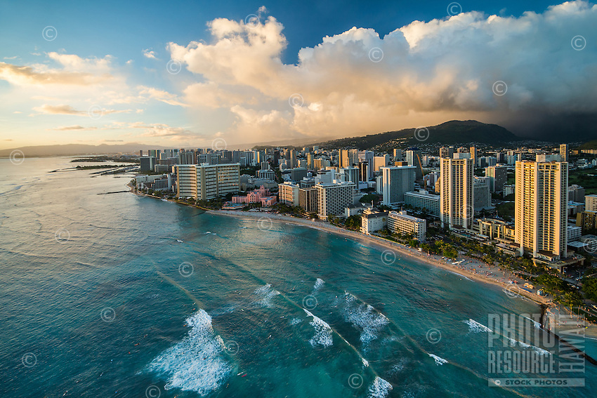Many beachgoers dot the shore to take in the sunset at Waikiki, O'ahu.