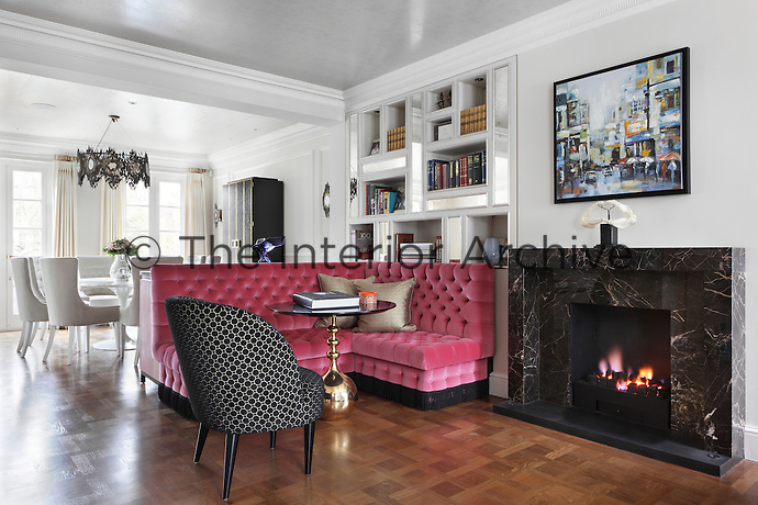 An informal dining area with pink banquette seating beside an open fireplace