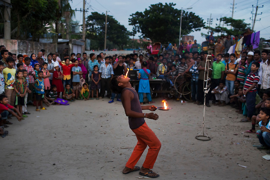 Bangladeshi children gather to watch a street acrobat perform a fire act at the Hazaribagh tannery area in Dhaka, Bangladesh.