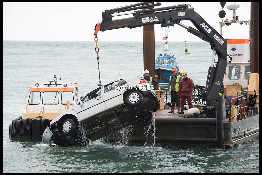 BNPS.co.uk (01202 558833)<br /> Pic: LauraDale/BNPS<br /> <br /> The car being lifted from the water.<br /> <br /> An elderly woman has today been rescued from her sunken car after she 'deliberately' drove into a harbour in front of stunned day-trippers.The motorist, aged in her 70s, wound down both windows of her Volkswagen Golf before speeding down a ferry slipway and into the water.As the silver car was swept 100 yards out to sea by the fast tide the woman sat motionless in the flooded driver's seat, ignoring cries from witnesses on the quayside to get out.A brave crew member of a passing fishing boat then dived into the water and pulled the woman free just moments before her vehicle completely sank.