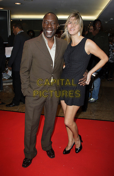 GARY BEADLE & TANYA FINDEL-HAWKINS.Screen Nation Film & Television Awards 2007, Hilton London Metropole, London, England..October 15th, 2007.full length brown suit black dress hand on hip married husband wife .CAP/ROS.©Steve Ross/Capital Pictures